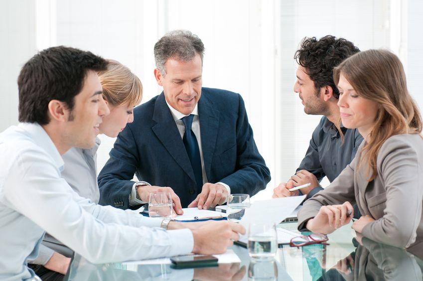 Ein Geschäftsmann und mehrere Mitarbeiter sitzen zusammen